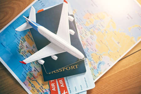 Photo pour Plane model with world map, passports and tickets as airplane traveling and tickets booking concept - image libre de droit