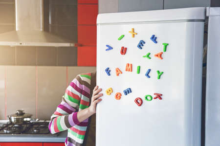Photo pour Woman looking in open fridge with Family letters on door. Cooking for children and husband concept - image libre de droit