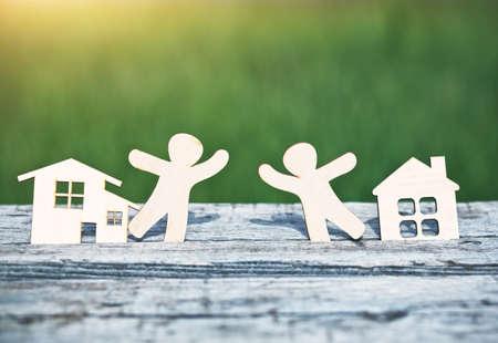 Photo pour little wooden men in houses. Symbol of neighborhood, friendship, teamwork and sweet home concept - image libre de droit