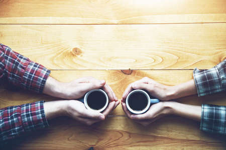 Photo pour Hands of couple with two cups of morning coffee on wooden table. View from above - image libre de droit