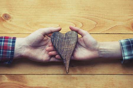Photo pour two hands holding wooden heart as symbol of love - image libre de droit