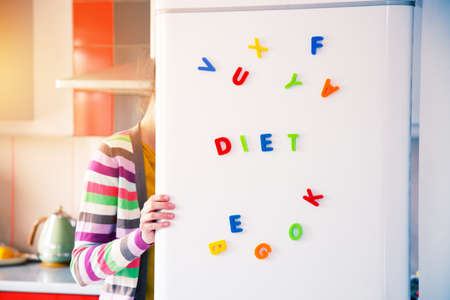 Photo pour hungry woman looking in open fridge with Diet letters on door - image libre de droit