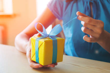 Photo for girl opening surprise gift box with ribbon - Royalty Free Image