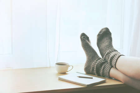 Foto de Woman resting keeping legs in warm socks on table with morning coffee and notebook. Space for text - Imagen libre de derechos