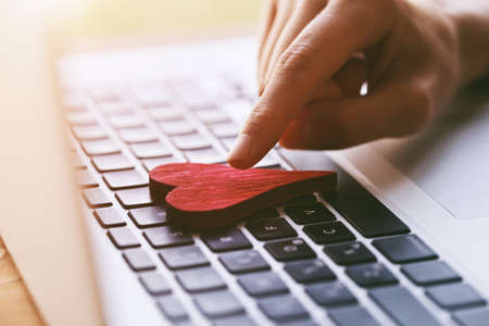 Photo pour hand giving heart with laptop as like symbol in social media for posts and photos - image libre de droit