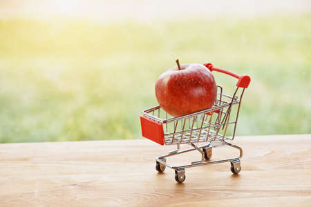 Photo pour toy trolley with apple as symbol of shopping and paying - image libre de droit