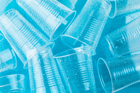 Photo for Empty transparent disposable plastic glasses in drops of water on bright blue background,  top view - Royalty Free Image