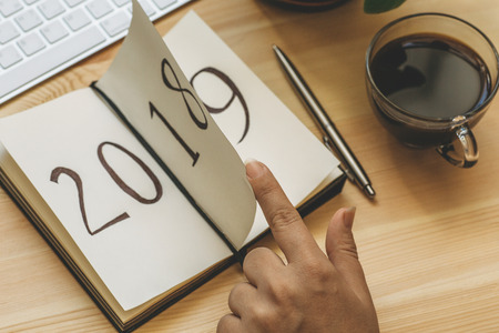 Photo pour New Year 2019 is coming concept. Female hand flips notepad sheet with finger on wooden table. 2018 is turning, 2019 is opening, toned - image libre de droit