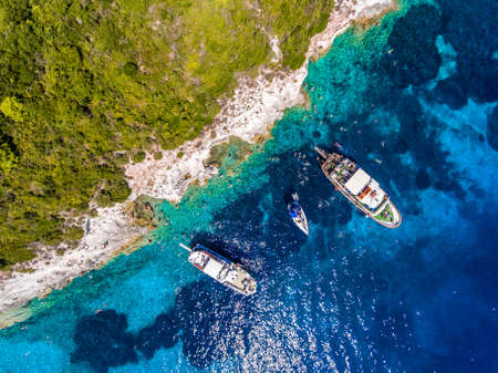 Foto de People swimming in the clear blue waters of Antipaxos Island, near Corfu - Kerkyra, Greece. Aerial view from a boat trip to the small island from Gaios town, Paxos. - Imagen libre de derechos