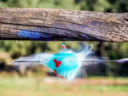 Foto de Balloons exploding when hit by an arrow. Closeup hi-speed shot. Arrow visible hitting the balloon - Imagen libre de derechos