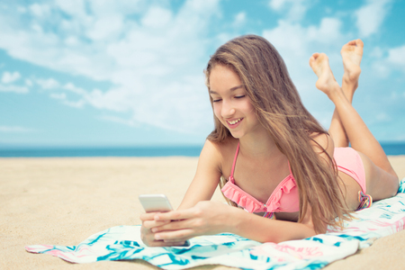 Photo pour Pretty teenager girl using a smart phone lying on the beach with the sea and horizon in the background - image libre de droit