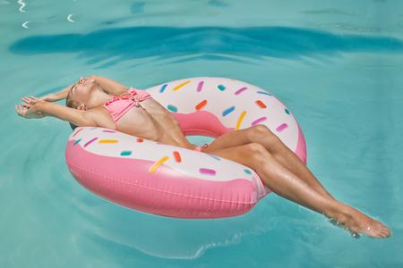 Photo pour Girl in bikini on the inflatable donut mattress in the swimming pool enjoying sunbath - image libre de droit