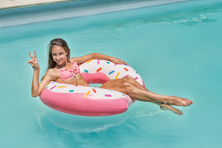 Photo pour Teenage girl have fun on inflatable donut in blue swimming pool - image libre de droit