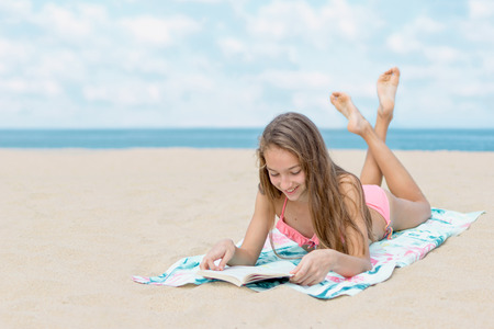Photo pour Pretty teenager girl reading book on the beach with the sea and horizon in the background - image libre de droit