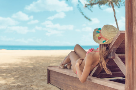 Foto de Young woman whit sun hat relaxing on sun bad enjoys sunbath at the beach with the sea and horizon in the background on hot summer day travel and tourism concept - Imagen libre de derechos
