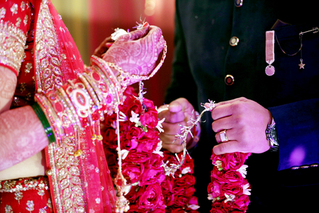 Photo pour The bride and groom at the Indian wedding garlands or Jaimala ceremony - image libre de droit