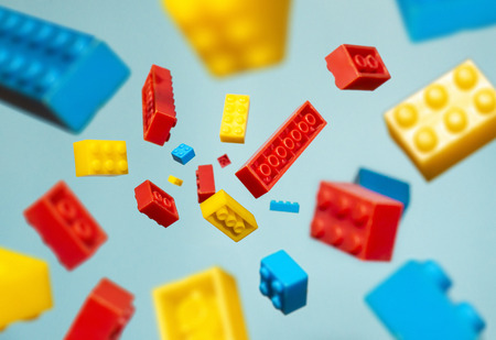 Foto de Floating Plastic geometric cubes in the air. Construction toys on geometric shapes falling down in motion.  Blue pastel background. Children's toys. Circle geometric shapes on plastic bricks. - Imagen libre de derechos