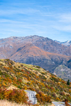 Photo pour Beautiful road between Queenstown and Wanaka via Crown range. Grassland autumn trees with beautiful landscape of rocky mountains. - image libre de droit