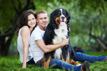 Young couple with a dog on the grass in the park