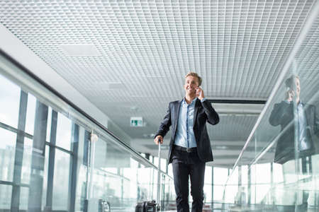 Businessman speaking on the phone at the airport