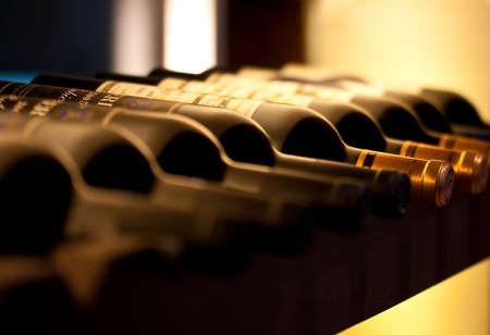 Photo pour Bottles of red wine on a wooden shelf - image libre de droit