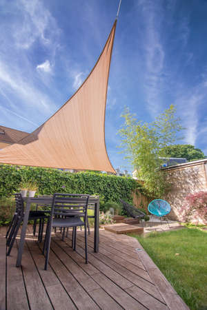 Foto de Modern house terrace in summer with table and shade sail - Imagen libre de derechos