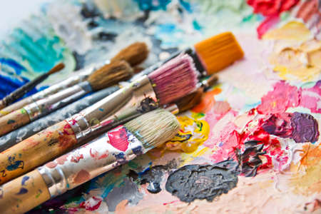 Photo for Used paint brushes on a colorful painter palette - Royalty Free Image