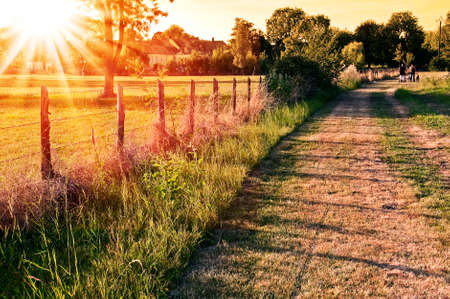 Photo pour Countryside landscape with a field and a village in the sunset - image libre de droit