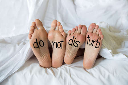 Photo pour Do not disturb written on the feet of a couple in a bed - image libre de droit