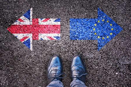 Photo pour Brexit, flags of the United Kingdom and the European Union on asphalt road with legs - image libre de droit