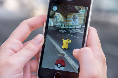 Photo pour CHAVILLE, FRANCE - JULY 24: Apple iPhone5s with Pikachu from Pokemon Go application, hands of a teenager playing on the first day of the launching of the game in France - image libre de droit
