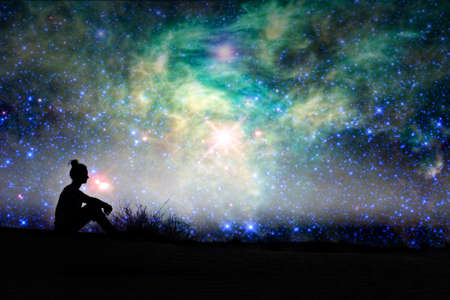 Photo for Silhouette of a woman sitting outside, starry night background - Royalty Free Image
