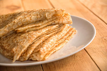 Foto de Close up on a stack of folded crepes (french pancakes) on a plate, wooden background - Imagen libre de derechos