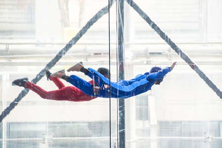 Photo pour Skydivers in indoor wind tunnel, free fall simulator - image libre de droit