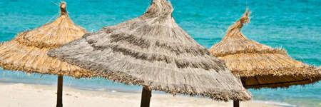 Foto de Panorama of beach umbrellas, turquoise sea bacground - Imagen libre de derechos