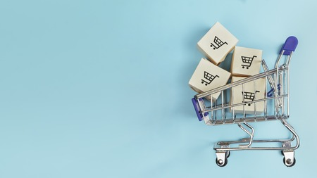 Foto de Boxes in a shopping cart on blue background. Concept: online shopping, e commerce and delivery of goods. Copy space - Imagen libre de derechos