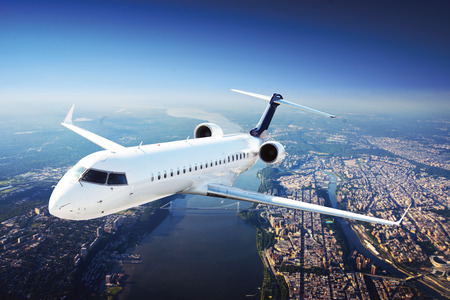 Foto de Private Jet Plane in the sky flying from city - Imagen libre de derechos