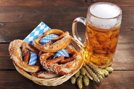 Foto de Original Bavarian Oktoberfest pretzels salted soft in a basket with beer from Germany on wooden board - Imagen libre de derechos