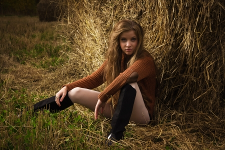 Pretty girl resting on straw bale on the autumn landscape background