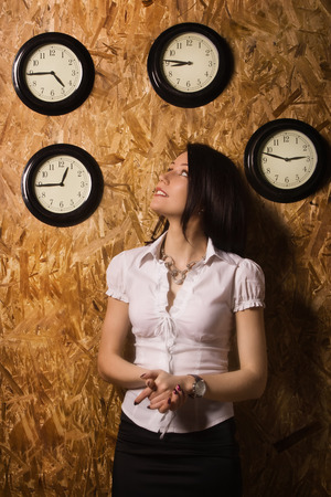 Confident office girl on a background of a wall clock