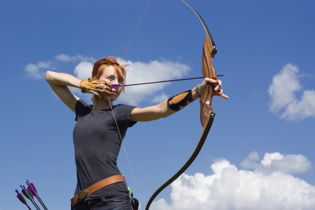 Photo for Archery woman bends bow archer target narrow in the summer field - Royalty Free Image
