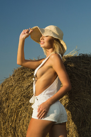 Photo pour beautiful young girl at a haystack in a summer field - image libre de droit