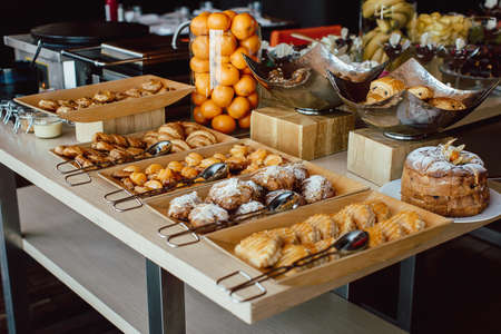 Photo for Assortment of fresh pastry and mandarin on table in buffet - Royalty Free Image