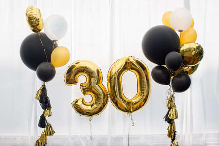 Foto de Decoration for birthday, anniversary, celebration of the thirtieth anniversary, white background, gold and black balloons with tassels - Imagen libre de derechos