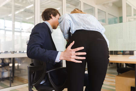 Photo for Back view of man molesting young girl at work putting hand on her bottom while working at table - Royalty Free Image