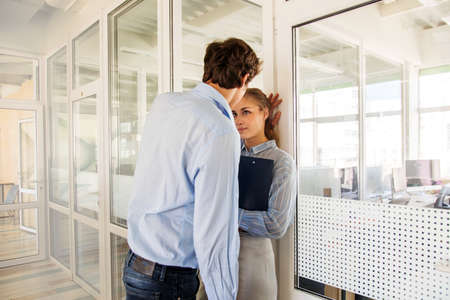 Photo for Formal man and woman flirting while standing in hall of office building having adultery - Royalty Free Image