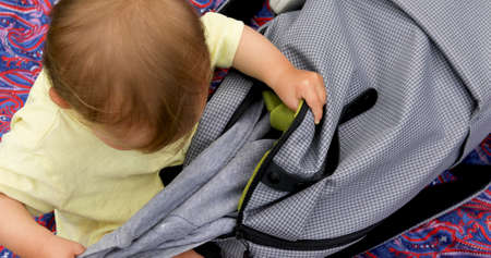 Foto per Baby look in bag that the search and gets out clothes and things of the bag - Immagine Royalty Free