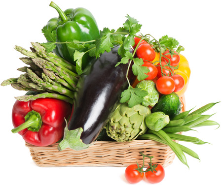 Composition with raw vegetables in a  wicker basket isolated on white
