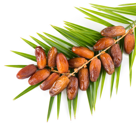 Foto de Top view of bunch of date fruits with palm leaf  isolated on white background - Imagen libre de derechos