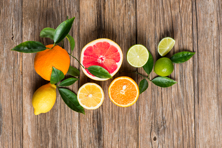 Photo for Twig with citrus fruits (grapefruit, orange, lemon, lime), top view on a rustic wooden background. - Royalty Free Image